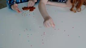 Dwa dziecka dekorują ciastka zbiory