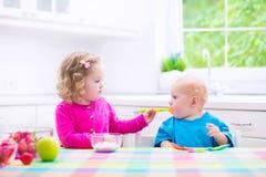 Dwa dziecka je jogurt Zdjęcia Royalty Free