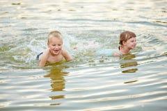 Dwa dziecka kąpać się w wodzie morze fotografia stock