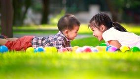 Dwa dziecka kłaść na zielonej trawie i uśmiechu Zdjęcie Stock