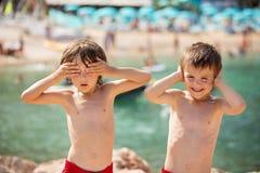 Dwa dziecka na plaży, chłopiec bawić się śmieszne twarze i robi, Obraz Stock