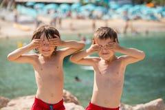Dwa dziecka na plaży, chłopiec bawić się śmieszne twarze i robi, Obraz Royalty Free
