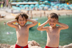 Dwa dziecka na plaży, chłopiec bawić się śmieszne twarze i robi, Fotografia Royalty Free