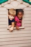 Dwa dziecka patrzeje przez okno w domek do zabaw Obrazy Stock
