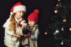 Dwa dziecka przy choinką, dziewczynami w ciepłych pulowerach i kapeluszami, zdjęcia stock