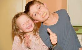 Dwa dziecka robią twarzom Chłopiec daje kciukowi up i dziewczyna klascze rytm Śmieszny i dzieci pojęcie Zdjęcia Royalty Free