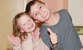 Dwa dziecka robią twarzom Chłopiec daje kciukowi up i dziewczyna klascze rytm Śmieszny i dzieci pojęcie Obrazy Stock