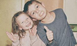 Dwa dziecka robią twarzom Chłopiec daje kciukowi up i dziewczyna klascze rytm Śmieszny i dzieci pojęcie dodaje Zdjęcie Royalty Free