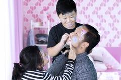 Dwa dziecka robi twarzy maluje ich ojciec zdjęcia stock