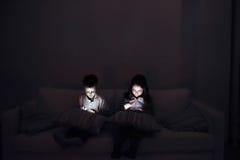 Dwa dziecka, siedzący w zmroku, bawić się z gadżetami Obrazy Royalty Free