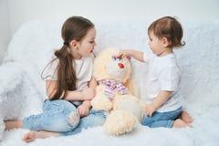 Dwa dziecka, siostry bawić się na białej kanapie w białych niebieskich dżinsach i koszulkach Miękki pluszowy królik zdjęcia stock