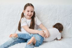 Dwa dziecka, siostry siedzą na białej kanapie w białych niebieskich dżinsach i koszulkach fotografia stock