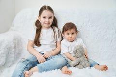 Dwa dziecka, siostry siedzą na białej kanapie w białych niebieskich dżinsach i koszulkach Miękki mokietu niedźwiedź fotografia stock