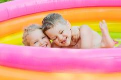 Dwa dziecka szczęśliwie unosi się w nadmuchiwanym pływackim basenie i śmia się Zdjęcie Royalty Free