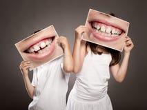 Dwa dziecka trzyma obrazek usta ono uśmiecha się obraz stock