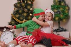 Dwa dziecka w Bożenarodzeniowych kostiumach ma zabawę Fotografia Stock