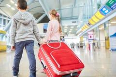 Dwa dziecka z bagażem w lotniskowy śmiertelnie obrazy royalty free
