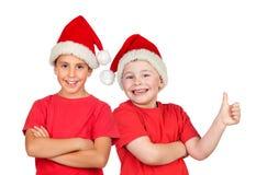 Dwa dziecka z Bożenarodzeniowym kapeluszem Obraz Royalty Free