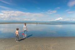 Dwa dziecka z piaska pail pozycją przy Centennial Wyrzucać na brzeg przy niskim przypływem fotografia stock