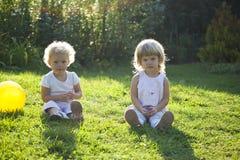 Dwa dziecko przeciw soczystej trawie w ogródzie Zdjęcia Stock