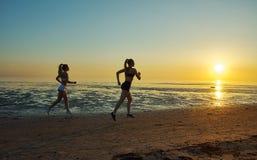 Dwa dziewczyn bieg morzem na plaży Zdjęcie Stock