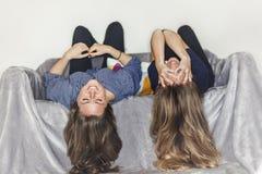 Dwa dziewczyn kłaść do góry nogami na popielatej kanapie ono uśmiecha się w domu obraz stock