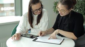 Dwa dziewczyn młody biznesowy spotkanie w kawiarni, wita each inny, siedzi przy stołowym okno praca lunch zbiory wideo