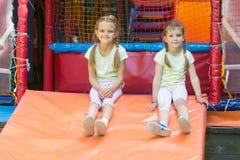 Dwa dziewczyn naprygalis dzieci sztuki miękki pokój odpoczywać i siedzący puszek Fotografia Royalty Free