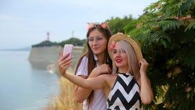 Dwa dziewczyn pozytywna blondynka w kapeluszu i brunetka z szkłami błaź się wokoło i robimy selfie obrazkom z telefonem zdjęcie wideo