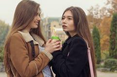 Dwa dziewczyn próba grzać up z gorącym napojem w outdoors Fotografia Royalty Free