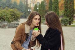 Dwa dziewczyn próba grzać up z gorącym napojem w outdoors Obraz Royalty Free