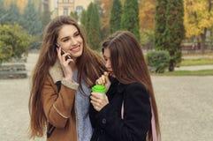 Dwa dziewczyn próba grzać up z gorącym napojem w outdoors Zdjęcia Royalty Free
