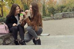 Dwa dziewczyn próba grzać up z gorącym napojem w outdoors Obrazy Royalty Free