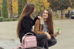 Dwa dziewczyn próba grzać up z gorącym napojem w outdoors Zdjęcie Stock