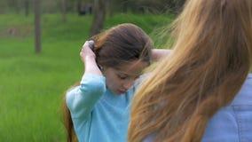 Dwa dziewczyn rozochocona mała blondynka i brown włosy czeszemy twój włosy outdoors blagierski długie włosy zbiory wideo