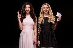Dwa dziewczyn Seksowna brunetka i blondynka pozuje z układami scalonymi w jej rękach, grzebaka pojęcia czerni tło Obraz Stock