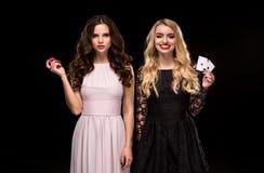 Dwa dziewczyn Seksowna brunetka i blondynka pozuje z układami scalonymi w jej rękach, grzebaka pojęcia czerni tło Obrazy Stock