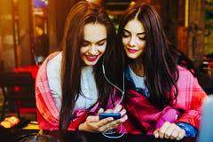 Dwa dziewczyn siedząca słuchająca muzyka Obraz Stock