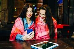 Dwa dziewczyn siedząca słuchająca muzyka Zdjęcie Stock