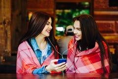 Dwa dziewczyn siedząca słuchająca muzyka Obraz Royalty Free