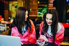 Dwa dziewczyn siedząca słuchająca muzyka Fotografia Stock