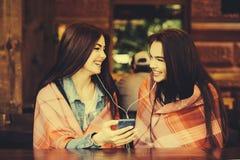 Dwa dziewczyn siedzący słuchanie muzyka Obraz Stock