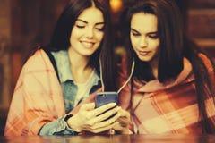 Dwa dziewczyn siedzący słuchanie muzyka Zdjęcia Stock