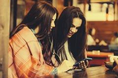 Dwa dziewczyn siedzący słuchanie muzyka Obrazy Stock