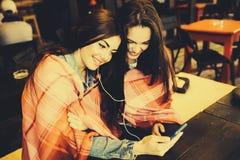 Dwa dziewczyn siedzący słuchanie muzyka z Zdjęcie Royalty Free