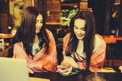 Dwa dziewczyn siedzący słuchanie muzyka z Zdjęcia Royalty Free