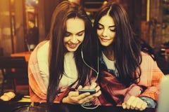 Dwa dziewczyn siedzący słuchanie muzyka z Obraz Stock