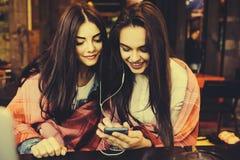 Dwa dziewczyn siedzący słuchanie muzyka z Zdjęcia Stock