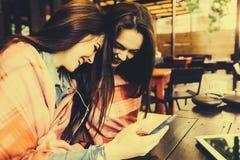 Dwa dziewczyn siedzący słuchanie muzyka z Zdjęcie Stock