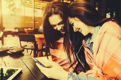 Dwa dziewczyn siedzący słuchanie muzyka z Obraz Royalty Free